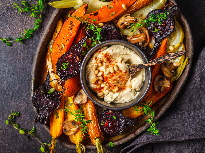 Baked carrots, beets, zucchini and yam with hummus in a dark dish