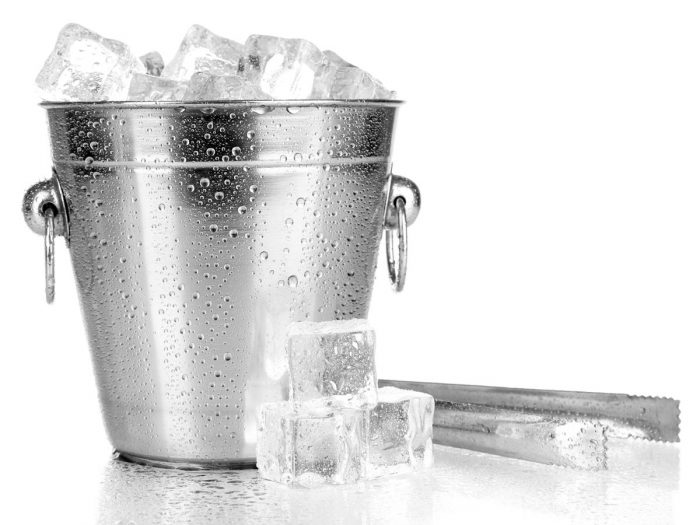 A bucket full of ice next to a steel tong