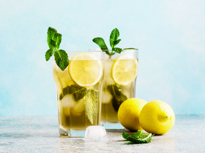 Iced green tea with lemon and fresh mint, with whole lemons