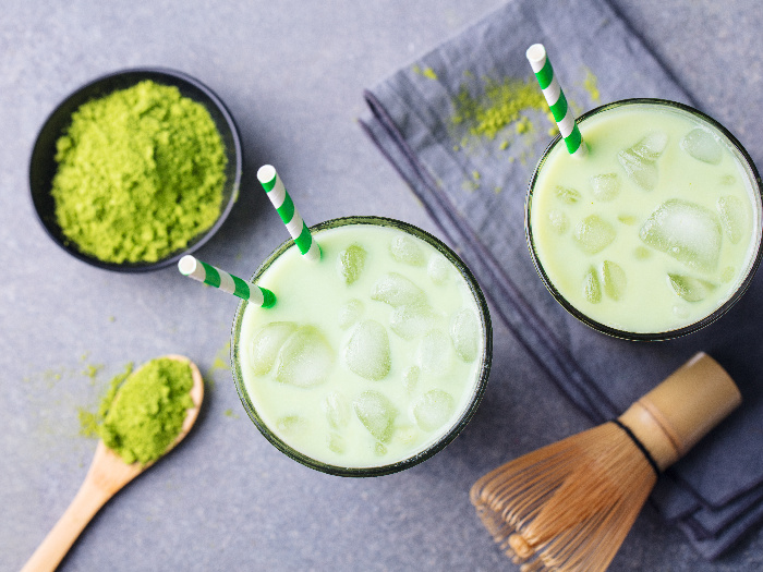 Matcha green tea ice latte with matcha powder and bamboo whisk