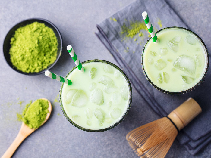 Matcha green tea ice latte with matcha powder and bamboo whisk, top view