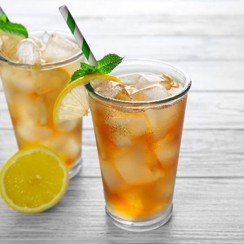 Two cocktail glasses filled with iced tea and garnished with mint leaves