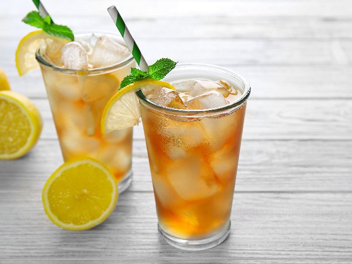 Two classes filled with lemon iced tea garnished with basil leaves and a straw