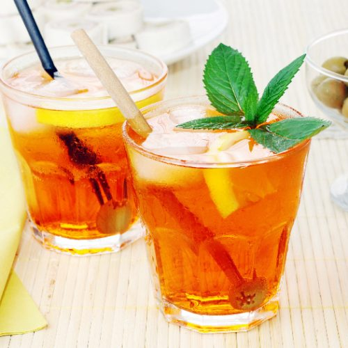Two small glasses filled with iced tea infused with fruits and mint