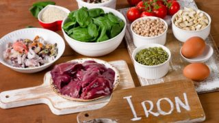 Iron rich foods (meat, fish, nuts, rice, pulses, cereals, eggs, tomatoes) on a wooden table
