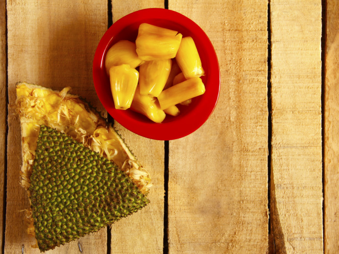 A red bowl of fresh jackfruit next to an empty jackfruit wedge