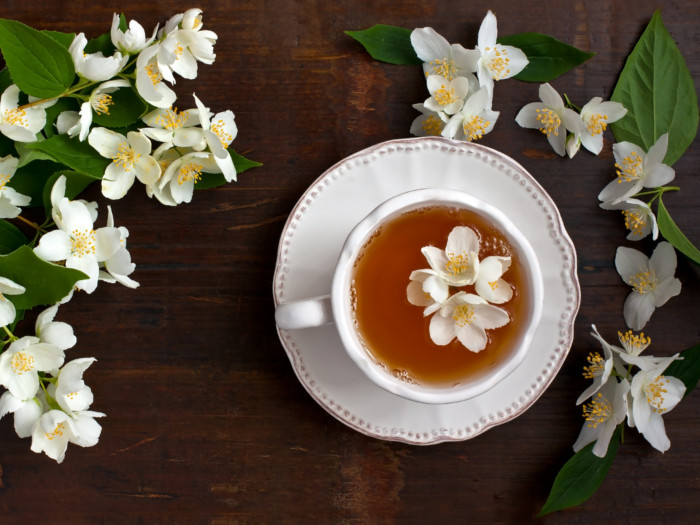 A cup with jasmine tea on a saucer, with fresh jasmine flowers next to it