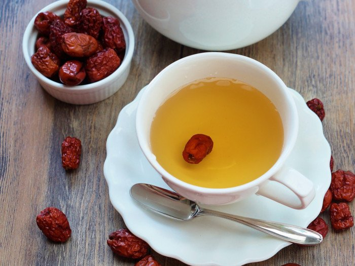 Jujube tea in a white cup placed on a wooden table, next to a small bowl filled with jujubes