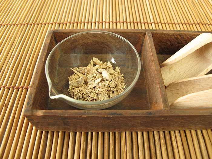 A bowl of kava tea kept in a wooden tray atop a cane platform