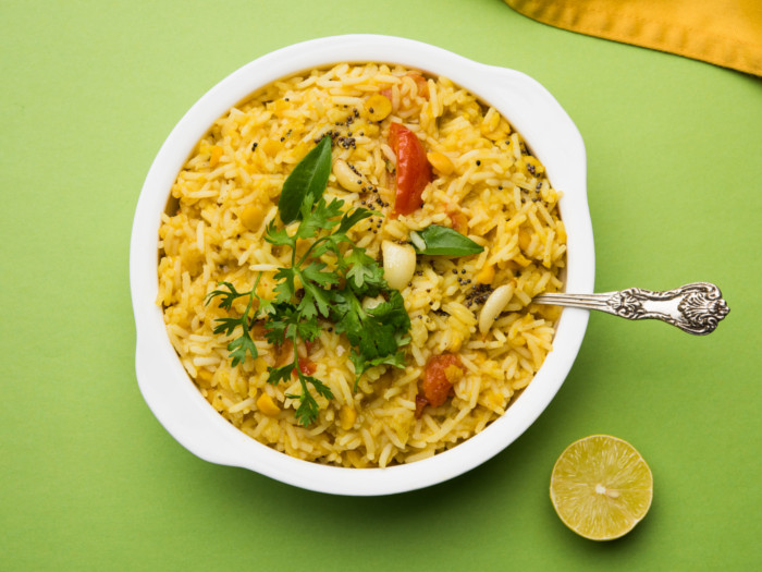 A plate of warm khichdi garnished with coriander and bay leaves on a light green placemat