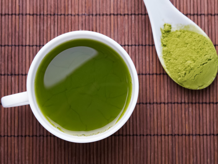 A cup full of tea accompanied by a spoonful of kratom powder