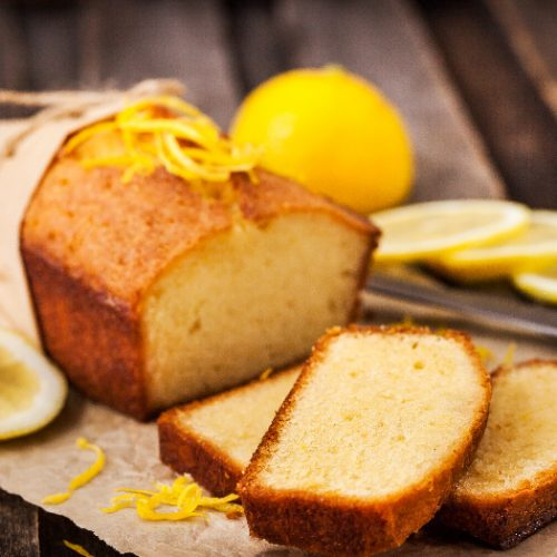 Lemon pound cake on rustic wooden background with lemon