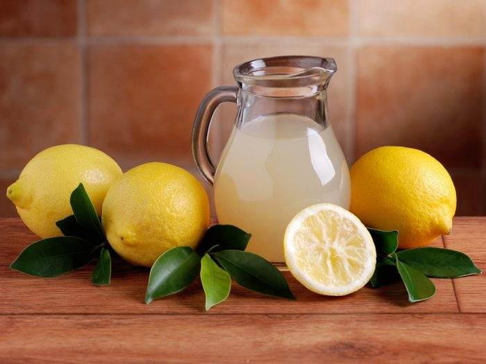 glass jar of lemon juice with lemons and lemon leaf on a wooden table