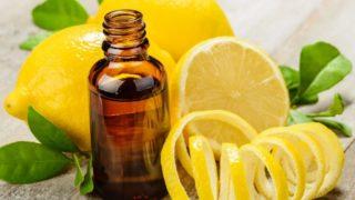 A bottle of lemon oil with peeled lemon and whole lemons