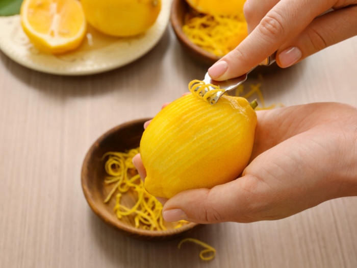 Scraping the lemon peel using a peeler