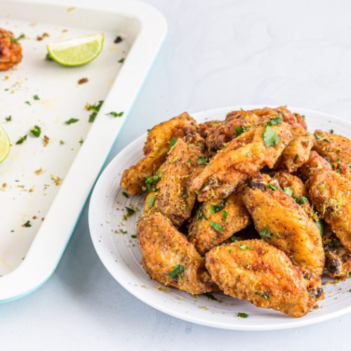 Crispy fried lemon pepper chicken wings on a white plate