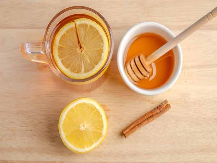 Lemon tea in a cup next to fresh lemon, honey, and cinnamon