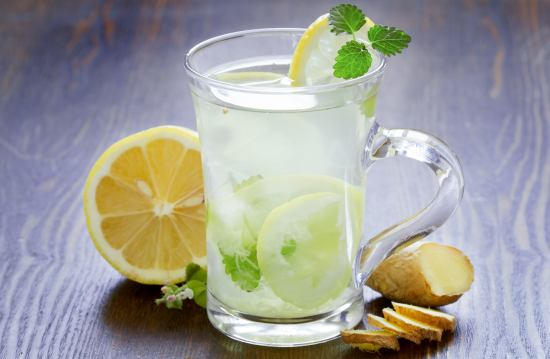 A glass of lemon water with slices of lemon, ice cubes, and mint in it.