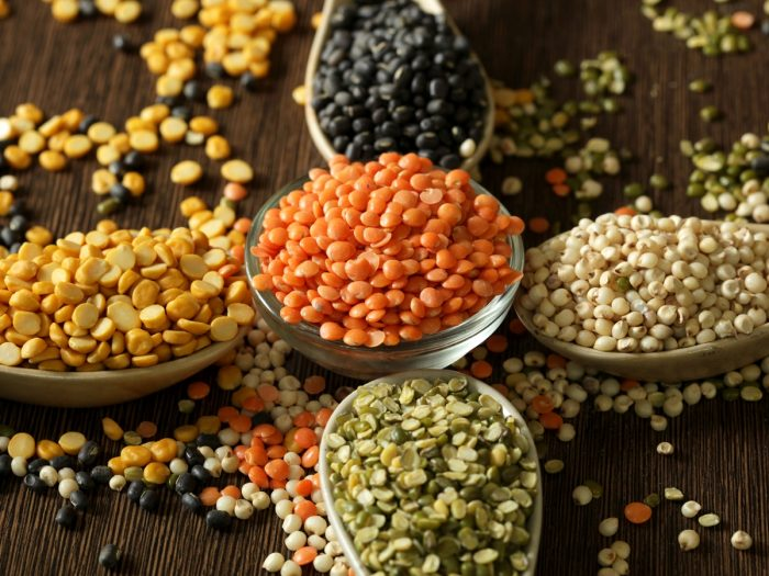 An assortment of various lentils in bowls and spoons