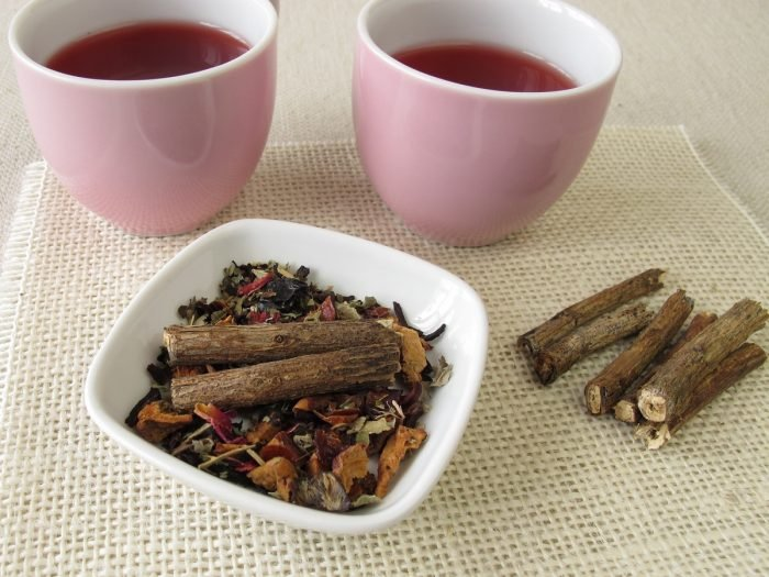 2 cups of licorice root tea, a white bowl of dried licorice roots on a mat