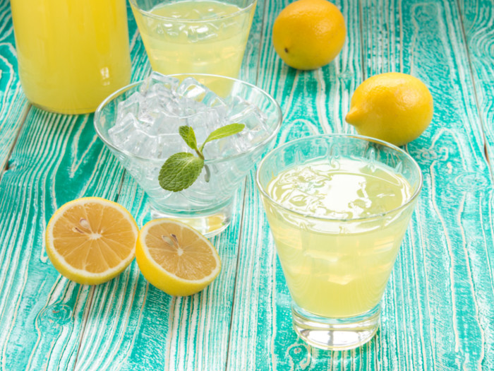 Glasses of limoncello kept besides lemons and a bowl of ice, atop a blue surface