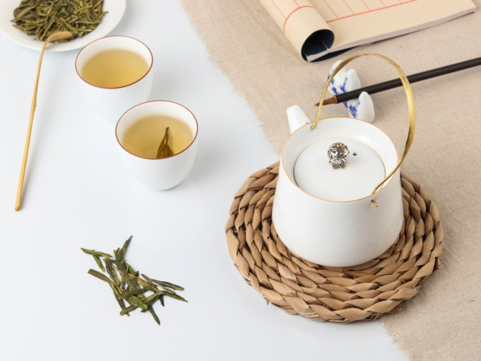 two small cups filled with longjing tea kept next to a tea kettle on a white table