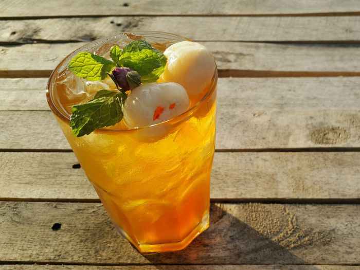 A glass of yellow-colored tea topped with mint and fruit, placed on a wooden platform
