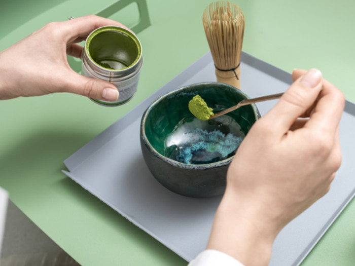 Close-up of someone holding a tin of matcha and a spoonful of matcha over a green ceramic bowl and a whisk placed nearby