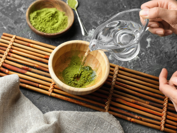 Someone pouring into a bowl of matcha placed on a bamboo mat with a bowl of matcha and spoon at the background.