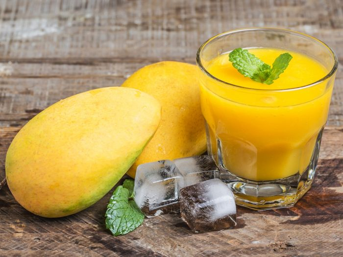 Mango juice in a glass, whole mangoes, and ice cubes on a wooden counter