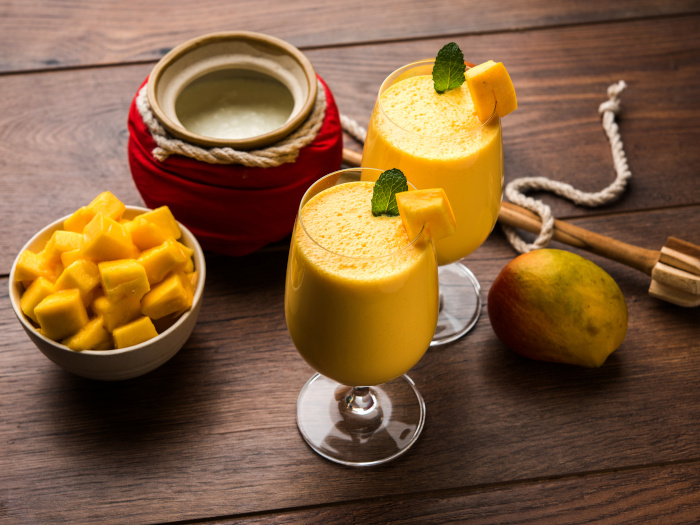 A close-up shot of mango lassi or smoothie in big glasses with curd, cut fruit pieces and blender