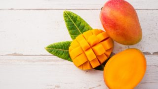 Fresh ripe mango - whole and sliced on a light wooden background