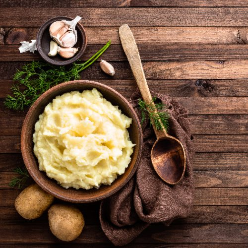 A flatlay picture of a plate of mashed potatoes placed next to two potatoes, brass spoon, napkin, garlic, atop a wooden table