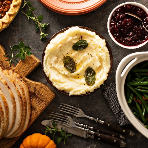 A flatlay picture of mashed potatoes with butter and sage, side dish for Thanksgiving or Christmas dinner, kept next to asparagus, baked beans and turkey slices.