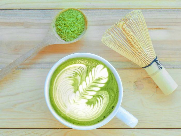 Flatline picture of a spoon of matcha powder, a cup of matcha tea and wooden whisk.