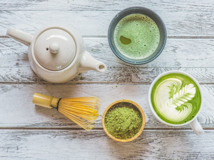Cups of matcha tea and matcha milk tea with a teapot, brewer, and matcha powder on a wooden table