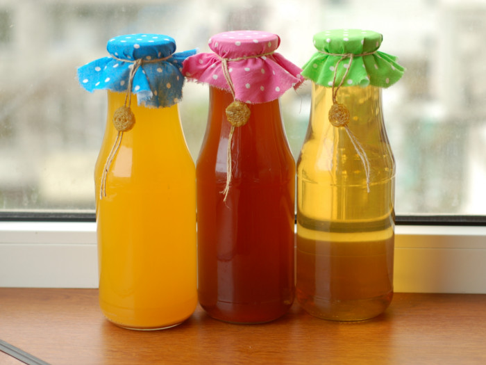 Different varieties of mead in glass bottles with colorful cloth lids