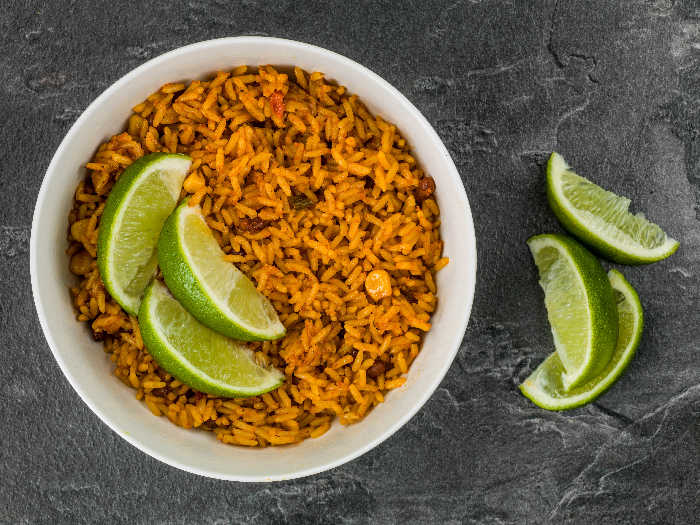 Bowl of Spicy Mexican Rice With Fresh Lime Against a Black Slate Tile Background