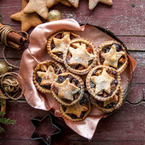 Mince pies in a vintage old plate with christmas decoration on wooden background