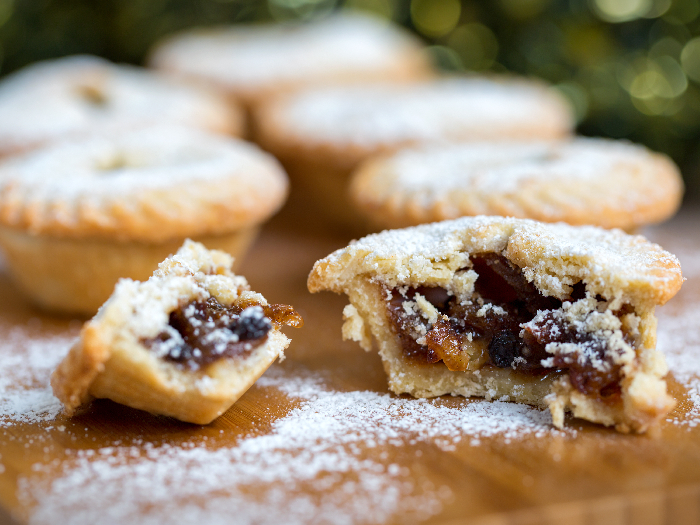 Closeup of an open mince pie on a wooden board with green christmas background