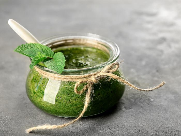 A close up shot of a jar containing mint sauce placed atop a grey platform