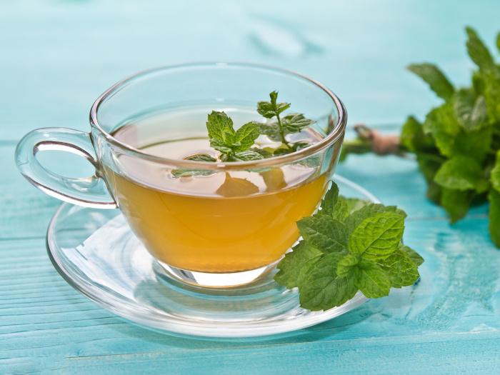 A close up shot of mint tea kept atop a blue platform