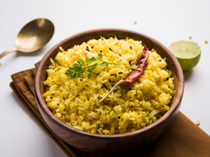 Spiced rice with coriander, mustard seeds, and red chili in a wooden bowl