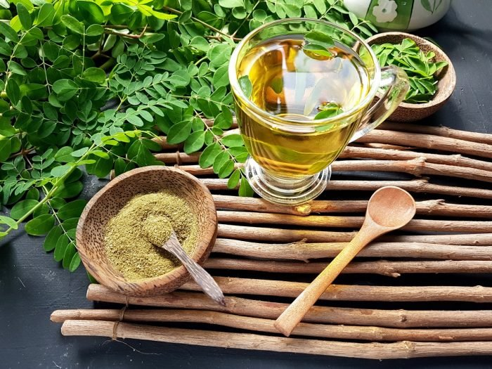 A cup of moringa tea with a wooden bowl of moringa powder and fresh leaves on wood sticks