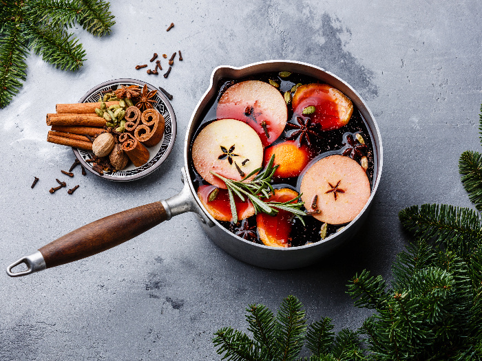 Mulled wine hot drink with citrus, apple, and spices in an aluminum casserole and Fir branch on concrete background