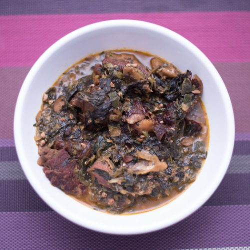 A white plate of Ogbono soup with mixed okra, dried fish and and bush meat on a purple mat