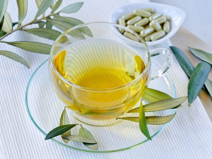 A close up shot of olive leaf tea, kept atop a white platform