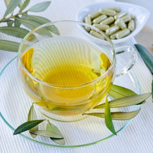 olive leaf tea in a glass cup and saucer with olive leaves and a dish of supplements