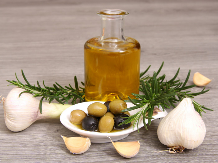 Olive oil bottle with herbs, whole garlic, green onion and olives