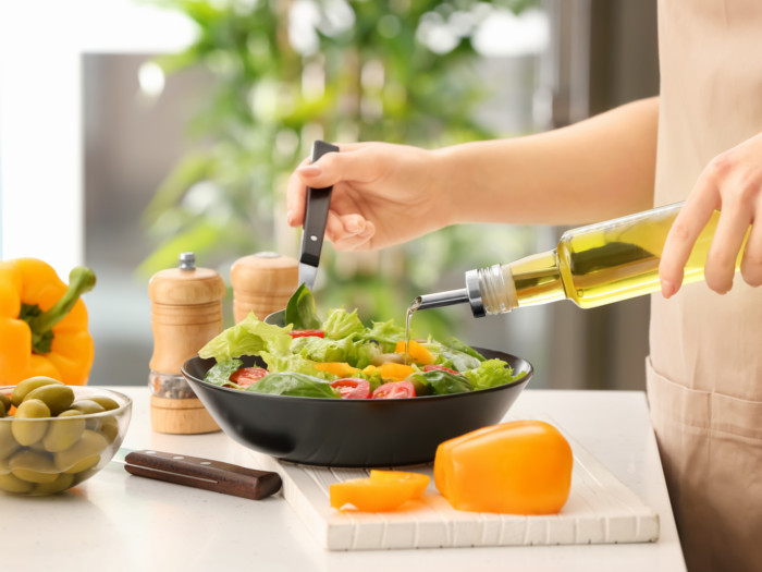 A woman drizzling olive oil on a green salad in a bowl kept on a white kitchen counter
